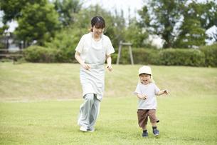 芝生で遊ぶ子供と女性の保育士の写真素材 [FYI04679888]