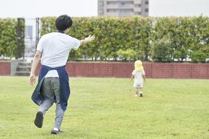芝生で子供を追いかける男性の保育士の写真素材 [FYI04679889]