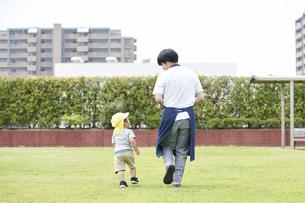 芝生で遊ぶ子供と男性の保育士の写真素材 [FYI04679890]