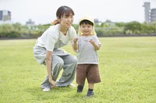 芝生で遊ぶ子供と女性の保育士の写真素材 [FYI04679892]