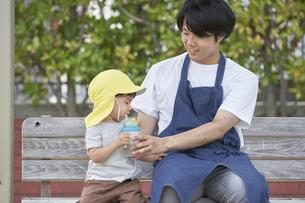 ベンチに座って子供にお茶を飲ませる男性の保育士の写真素材 [FYI04679894]