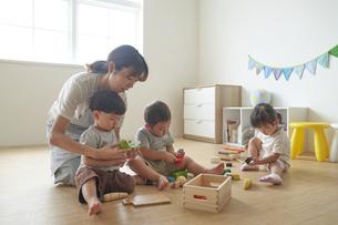 おもちゃで遊ぶ子供たちと女性の保育士の写真素材 [FYI04679895]