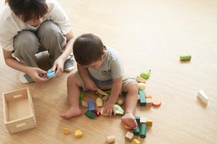 おもちゃで遊ぶ子供と女性の保育士の写真素材 [FYI04679896]