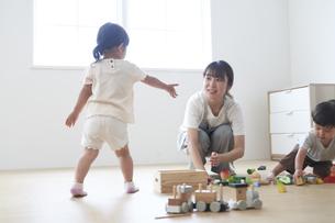 おもちゃで遊ぶ子供と女性の保育士の写真素材 [FYI04679897]