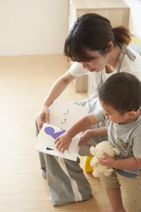 子供に絵本を読み聞かせる女性の保育士の写真素材 [FYI04679899]