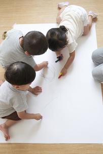 床でお絵描きをする子供たちの写真素材 [FYI04679900]