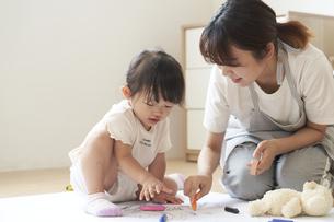 床でお絵描きをする子供と女性の保育士の写真素材 [FYI04679901]