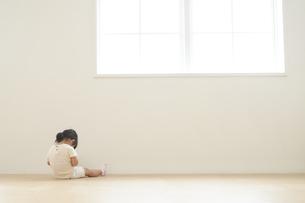 部屋の隅に座る子供の後ろ姿の写真素材 [FYI04679908]
