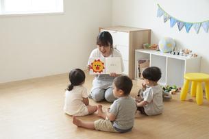 子供達に絵本を読み聞かせる女性の保育士の写真素材 [FYI04679909]