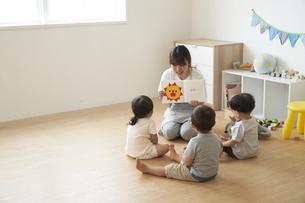 子供達に絵本を読み聞かせる女性の保育士の写真素材 [FYI04679910]