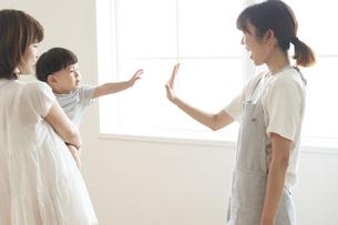 帰宅する子供に手を振る女性の保育士の写真素材 [FYI04679912]
