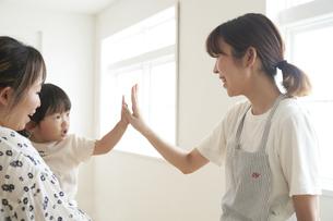 帰宅する子供とタッチをする女性の保育士の写真素材 [FYI04679914]