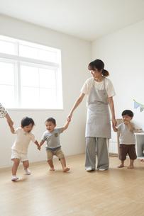 子供たちと手を繋ぐ女性の保育士の写真素材 [FYI04679915]