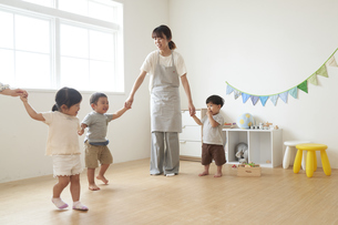 子供たちと手を繋ぐ女性の保育士の写真素材 [FYI04679916]