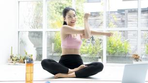 パソコンを見ながら自宅で運動する綺麗な女性の写真素材 [FYI04680098]