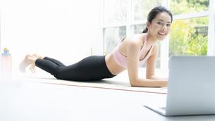 ノートPCを見ながら自宅で運動する若い女性の写真素材 [FYI04680099]