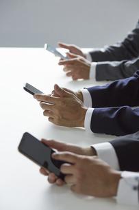 スマートフォンを触っているビジネスマンの写真素材 [FYI04680169]