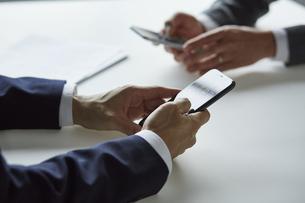 スマートフォンを持っているスーツを着た男性の写真素材 [FYI04680184]