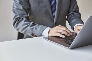 ノートパソコンを触っているビジネスマンの写真素材 [FYI04680276]