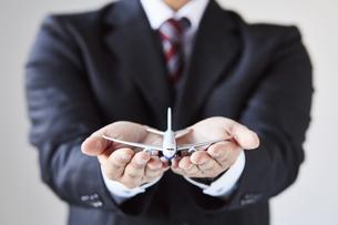 飛行機の模型を持っているスーツを着た男性の写真素材 [FYI04680287]