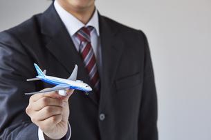 飛行機の模型を持っているスーツを着た男性の写真素材 [FYI04680288]