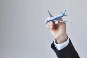 飛行機の模型を持っているスーツを着た男性の写真素材 [FYI04680289]