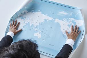 世界地図を広げているスーツを着た男性の写真素材 [FYI04680292]