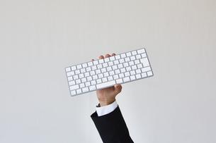 キーボードを持っているスーツを着た男性の写真素材 [FYI04680293]