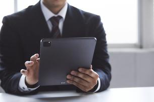 タブレット端末を見ているスーツを着た男性の写真素材 [FYI04680301]