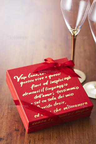 シャンパングラスと赤色のプレゼントボックスの写真素材 [FYI04680433]