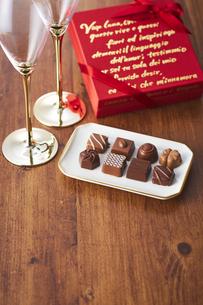 シャンパングラスと赤色のプレゼントボックスとチョコレートの写真素材 [FYI04680434]
