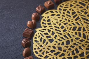 黒い皿の上に置かれたチョコレートと金色の模様のマットの写真素材 [FYI04680438]