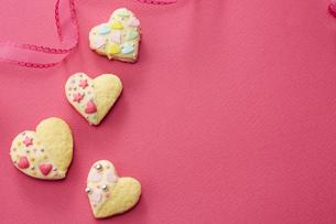 ピンクの紙の上に置かれた手作りクッキーの写真素材 [FYI04680466]