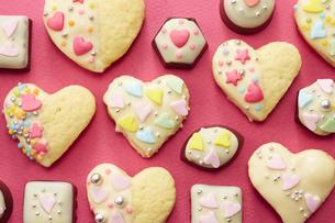 ピンクの紙の上に置かれた手作りクッキーとチョコレートの写真素材 [FYI04680472]