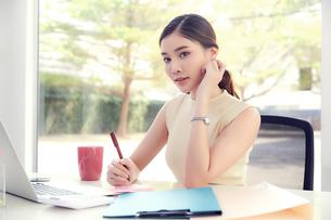 若い女性社員がデスクで仕事しているの写真素材 [FYI04680523]