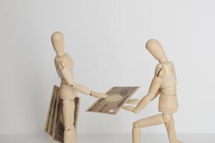 マージンを取る悪徳業者と頭を下げて受け取る人の人形の写真素材 [FYI04680619]