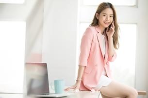デスクに腰を掛けながら携帯電話で通話する若い女性会社員の写真素材 [FYI04680621]