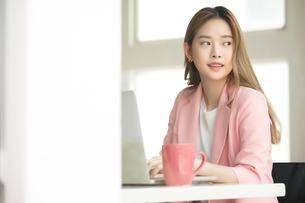 オフィスでノートパソコンで仕事している若い女性社員の写真素材 [FYI04680627]