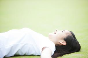 グラウンドに寝そべる女の子の写真素材 [FYI04681511]