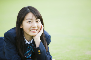 芝生で頬杖をつく女子高生の写真素材 [FYI04681525]