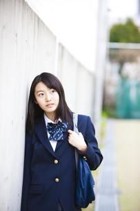 壁にもたれ掛かる女子高生の写真素材 [FYI04681526]