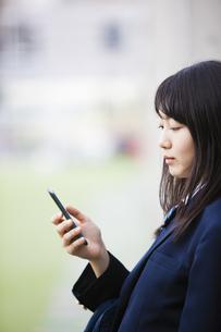 スマートフォンをいじる女子高生の写真素材 [FYI04681528]