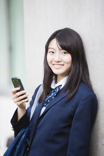 スマートフォンをいじる女子高生の写真素材 [FYI04681529]