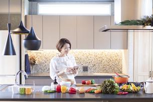 レシピを見ながら料理する女性の写真素材 [FYI04681575]