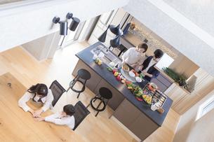 キッチンに立つ夫婦と喋る姉弟の写真素材 [FYI04681583]
