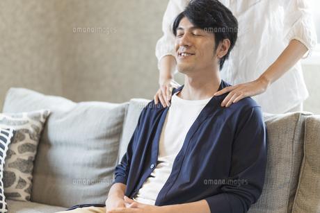 夫の肩を揉む妻の写真素材 [FYI04681615]
