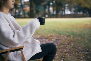 森でホーローカップを持ちイスに座り休憩する女性の写真素材 [FYI04681618]