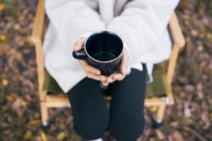 森でホーローカップを持ちイスに座り休憩する女性の写真素材 [FYI04681619]