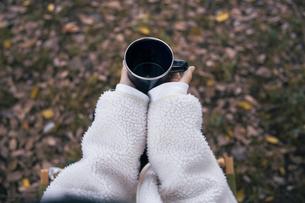 森でホーローカップを持ちイスに座り休憩する女性の写真素材 [FYI04681620]