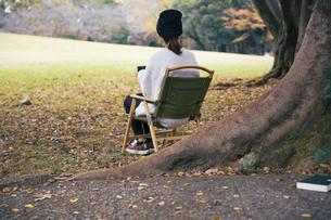 森でホーローカップを持ちイスに座り休憩する女性の写真素材 [FYI04681621]